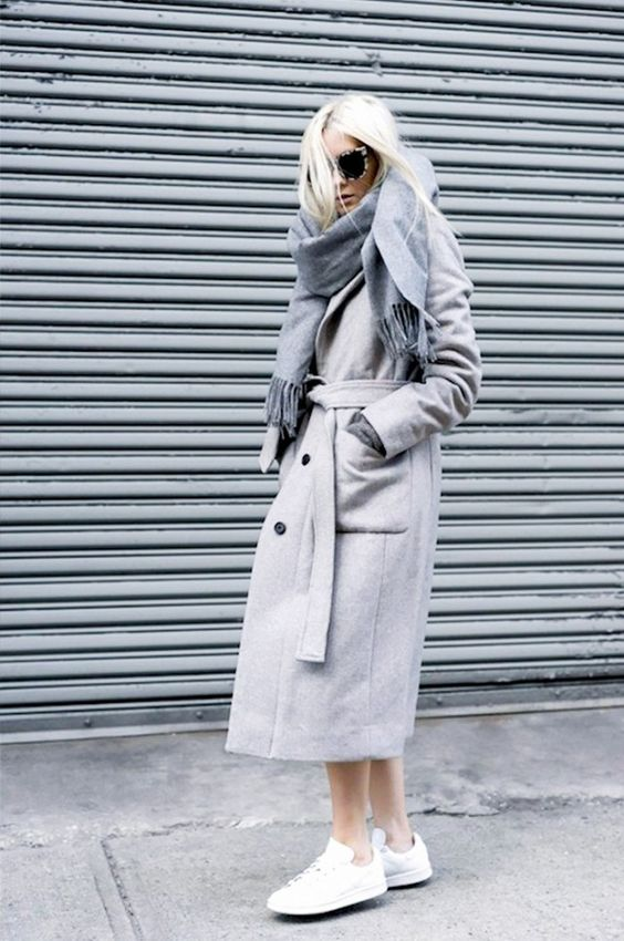 A gray trench coat is paired with a darker gray scarf, white sneakers, and cat-eye sunglasses