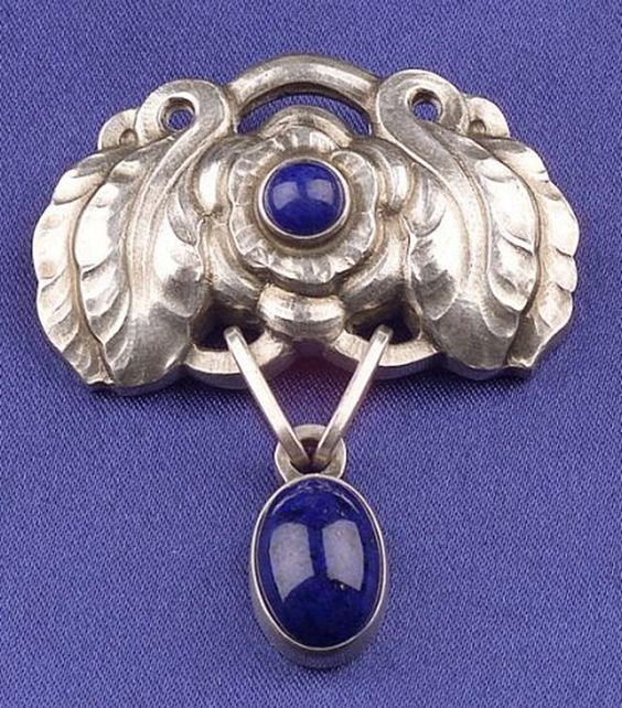 Georg Jensen. Design no. 193. Sterling silver and lapis lazuli brooch, with flower and leaf motifs, bezel-set lapis lazuli cabochons, length. 1 3/4 in., signed.