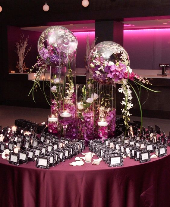Glass cylinder decorations overflowing with exotic flowers for Glass tables for wedding reception