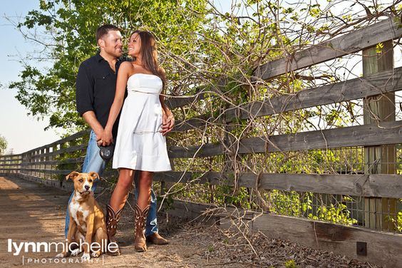 Country chic engagement portraits. Rustic fence, cowboy boots, puppy dog.