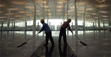 Two workers mop the floor in Beijing airport's newly-built Terminal Three. Photograph: Victor Liu/EPA