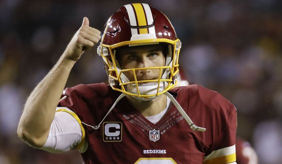 Washington Redskins quarterback Kirk Cousins (8) signals a thumbs up as he…
