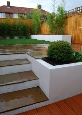 Few Steps up built leading to the garden area with Indian Sandstone Patio Design and nice new Lawn.