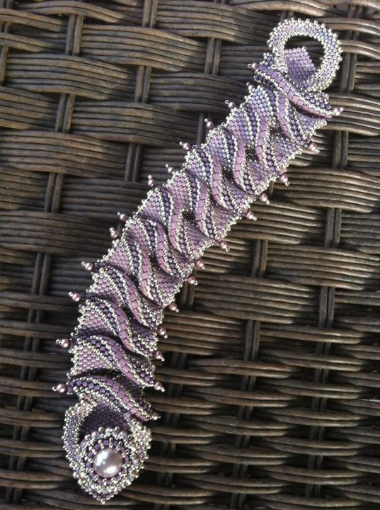 I think the pleats are stitched in place after beading and folding, followed by creating a picotee edge.