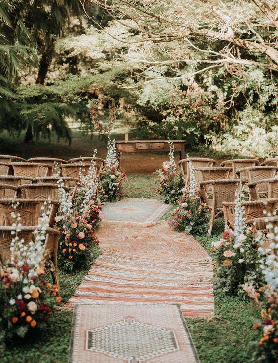 Boho Hochzeit im Garten - mit Vintage Tisch, Korbstühlen, Teppichen und bunten Wildblumen, die den Weg säumen. #bohohochzeit #hochzeitsdekoboho #hochzeitsdekooutdoor #hochzeitsdekowildblumen #hochzeitsblumen