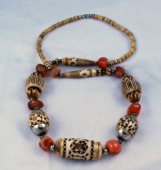 Vintage bone and agate necklace - This is a fabulous extra long necklace that is made from hand carved bone beads in a variety of shapes and sizes as well as some genuine red agate beads. The bone beads are very nicely carved with pierced and fluted designs, the bone is also dyed to give it some depth and accents. In between the bone and agate are some silver tone beads and bead caps too. It has a silver tone barrel screw clasp.