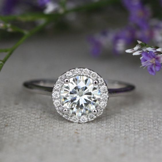 This halo engagement ring is crafted in solid 14k white gold featuring a 7x7mm round cut Forever Brilliant Moissanite surrounded by sparkling