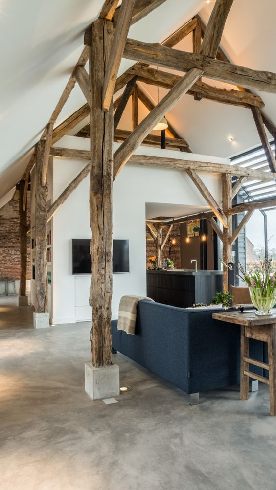 Rustic elegance in an #industrialfarmhouse living space with gorgeous beams, concrete floors, and modern design.