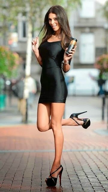 Stork pose in a little black dress and platform high heels ...