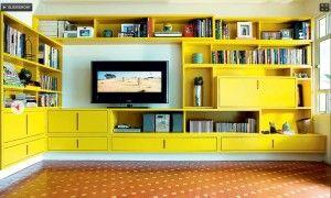 Estante de MDF com acabamento em gofrato amarelo. Para amenizar o visual marcante a base da estante foi pintada de branco, dando a impressão de que o móvel está suspenso