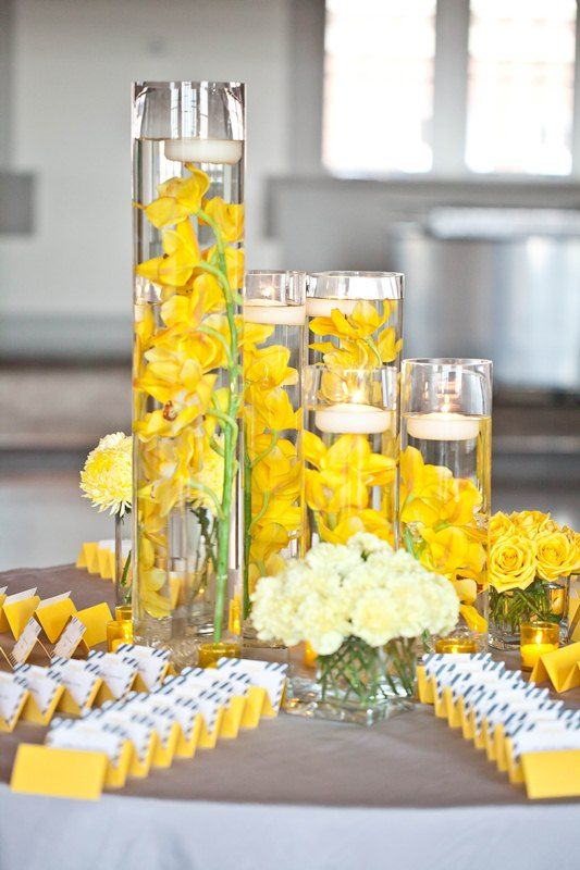 Yellow orchids white floating candles in tall glass