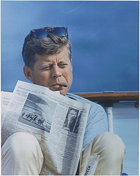 Spending the weekend in Hyannisport aboard his ship the Honey Fitz , Kennedy smokes a cigar and reads The New York Times .