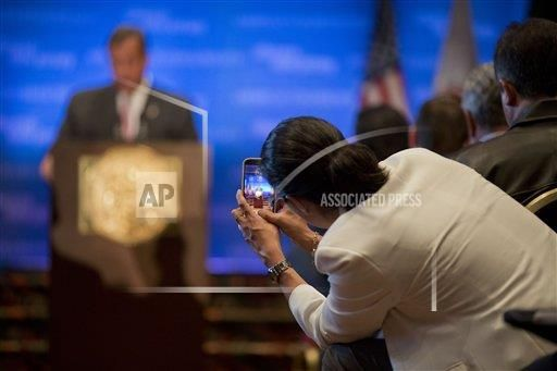 A woman leans out into the aisle to take a cell phone picture of New Jersey Gov. Chris Christie, as he addresses the American Chamber of Commerce in Mexico, in Mexico City, Wednesday, Sept. 3, 2014. Christie took a spin on the international stage Wednesday, bringing state business to Mexico City and testing his diplomatic savvy as he considers a run for U.S. president in 2016. (AP Photo/Rebecca Blackwell)