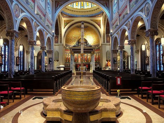 St. Anthony Cathedral Basilica - Beaumont, Texas. Looking down the center aisle of the church, you'll see the Baptismal Font followed by 7 Virtues of the Catholic Church in hand-laid tile.