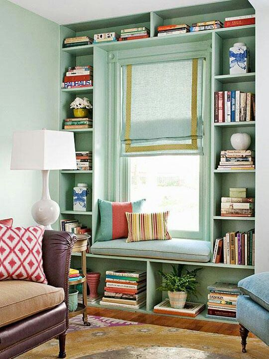 built in bench under window surrounded by book shelves