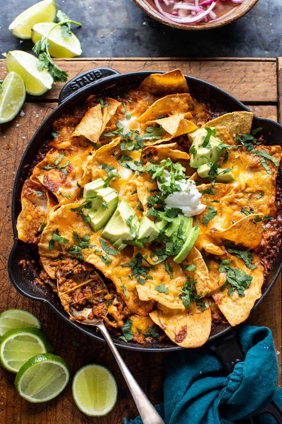 One Skillet Saucy Chicken Tortilla Enchilada Rice Bake. Mexican seasoned chicken, rice, and enchilada sauce topped with tortilla chips and plenty of cheese!