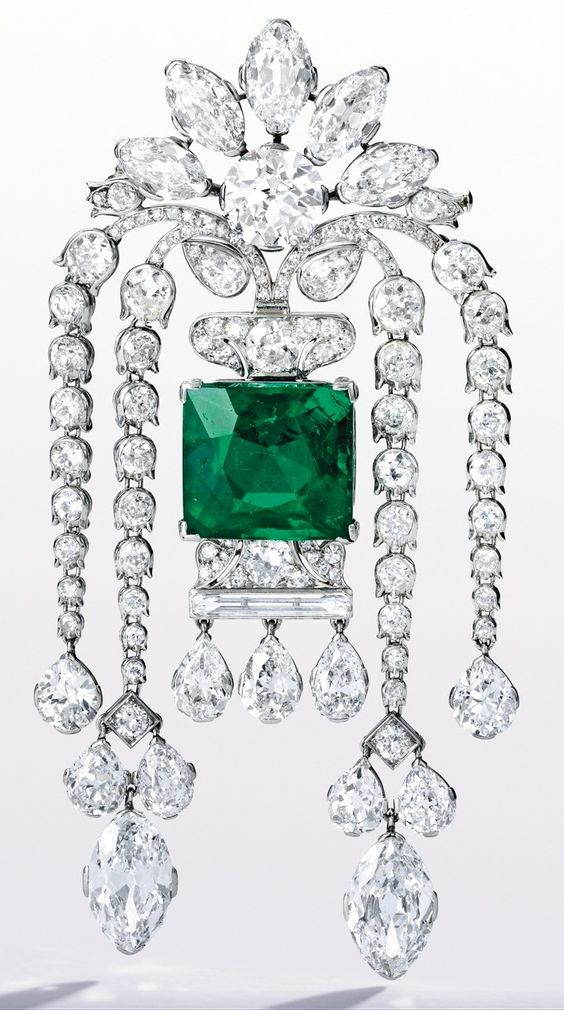PLATINUM, EMERALD AND DIAMOND BROOCH. Centred by a modified emerald-cut emerald weighing 22.48 carats, topped by a round diamond weighing approximately 3.70 carats, framed by five marquise-shaped diamonds, suspending four undulating fringes set with two marquise-shaped diamonds and nine pear-shaped diamonds, accented throughout with old European, single-cut, pear-shaped and baguette diamonds, circa 1920.