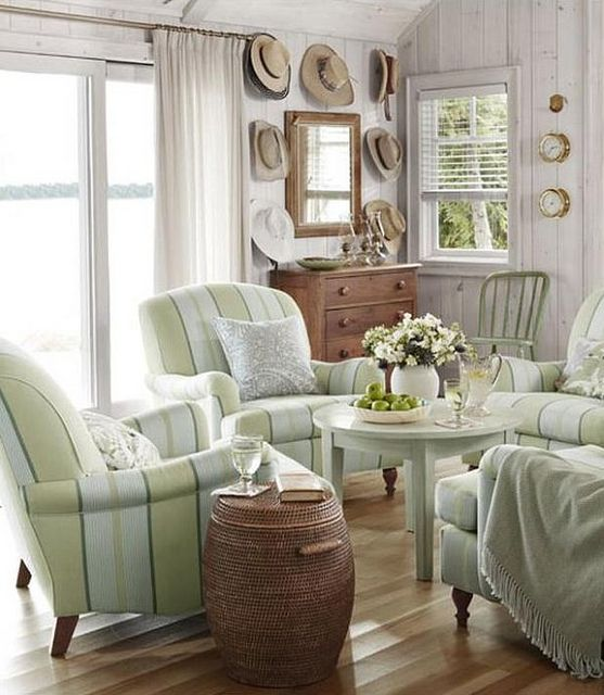 Sarah Richardson Cottage with cheerful green club chairs, hats hung on wall, and whitewashed paneling. #cottage #sarahrichardson #beachhouse
