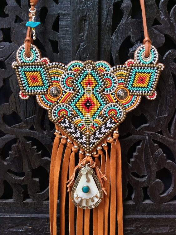 A beaded tribal style necklace featuring colorful glass seed beads, brass and silver metal beads hand sewn onto a bib of soft saddle tan leather.