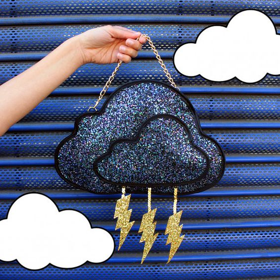 A storm cloud shaped clutch handbag.  The 2D cloud is made from a petrol coloured glitter fabric, bound in black satin and lined in black silk