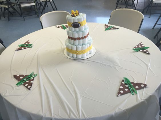 Table decorations at football inspired baby shower. Diaper cake includes football rubber duckies and football ribbons.