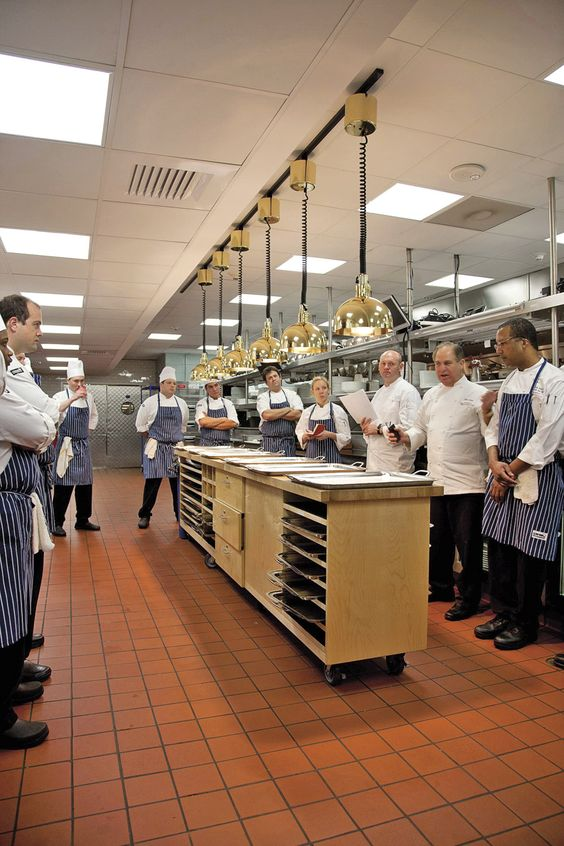 John Folse holds a kitchen staff meeting around the runners' station in the kitchen. - Sara Essex Bradley