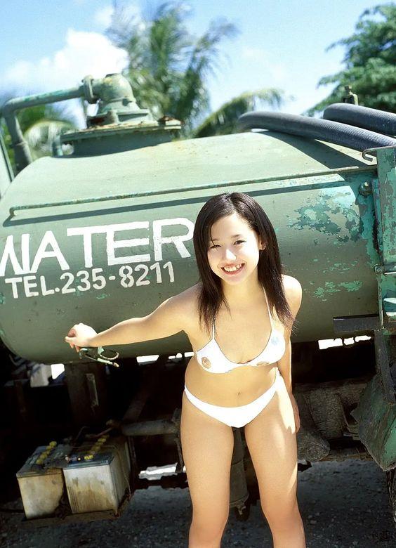 白いビキニを着て緑の車の前に立つ沢尻エリカの画像