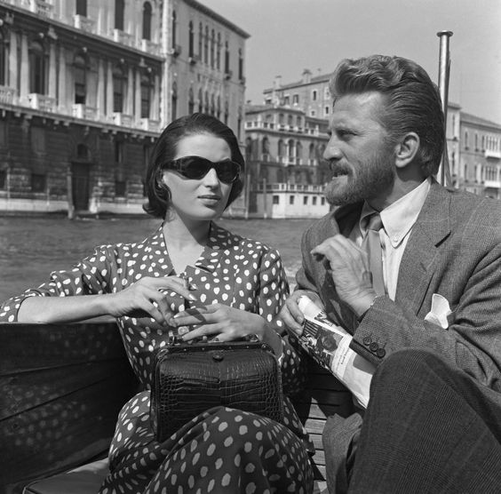 American actor Kirk Douglas sits on a water taxi next to Italian actress Silvana Mangano on the Canal Grande in Venice, Italy, circa 1953.