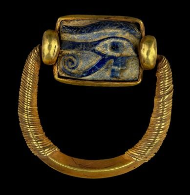 An ancient Egyptian gold and lapis-lazuli swivel ring containing wedjat amulet, a symbol of wholeness and wellbeing.