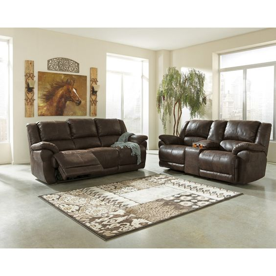 Ashley Garthay Two Piece Power Reclining Sofa Set - The Garthay-Sable upholstery collection features stylishly shaped padded arms along with divided back cushioning and pad-over-chaise seating all surrounded within a rich faux leather upholstery fabric adorned with dramatic stitched detailing to create the ultimate fusion of contemporary design and relaxing comfort.