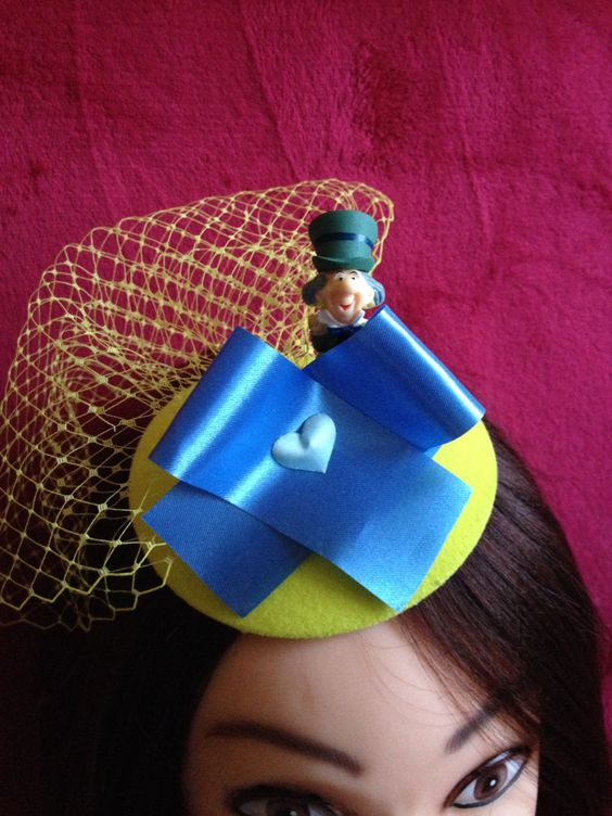 Sunny yellow and blue hat consists of a yellow base, yellow veil, a blue ribbon, blue heart and figure of Mad Hatter. Magnificent hat. #Minihat #veil #Carnival #Halloween #Christmas #ValentineDay #NewYear #costumeparty #minihats #Alice #AliceintheWonderland #MadHatter