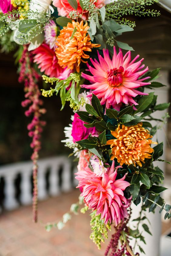 Colourful wedding flowers over the archway at Marleybrook House - Walled Garden ceremony area. Pink and orange wedding theme. Photography by Terri Pashley.
