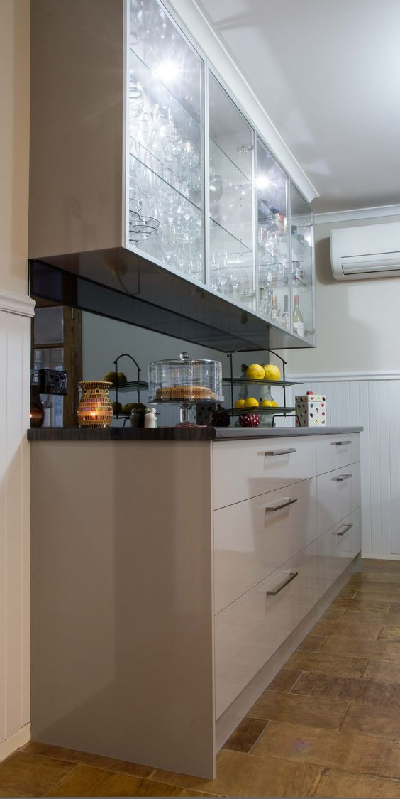 Buffet bar. Modern style. Smoked mirror splashback. Glass overhead cabinet  doors. www