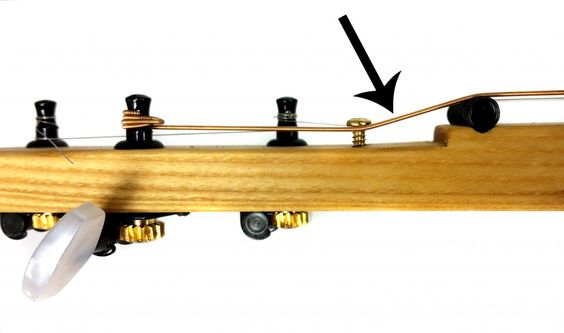 "This photo shows how retaining screws can be used to adjust the ""break angle"" of the strings - the angle at which they cross over the nut/zero fret. While this photo shows an unfretted cigar box guitar that uses a threaded rod nut, the same concept applies to a guitar using a zero fret."