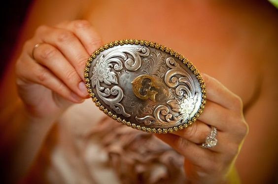Blushing bride shows off diamond engagement ring, holds groom's belt buckle