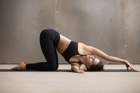 Young attractive woman in thread the needle pose, grey studio
