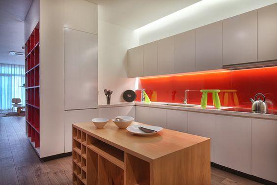 Hệ tủ được thiết kế gấp khúc sát tường trong không gian sinh hoạt chung. Tủ có tác dụng phân chia và xác định không gian bếp, ăn và khách. Bàn bếp nhiều ngăn để đồ có thể di chuyển khi cần thiết.