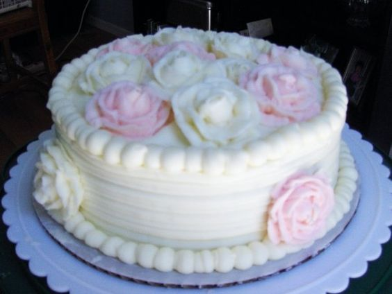 Decorated with buttercream frosting.  The roses are buttercream and were done on a rose nail and then frozen before being placed on the cake.