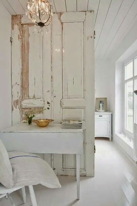 A gorgeously weathered old door becomes a partition in a bedroom. Weathered Walls & Déshabillé Lovely. #NordicFrench #shabbychic #Scandinavian #farmhouse #weathered #doors #whitedecor