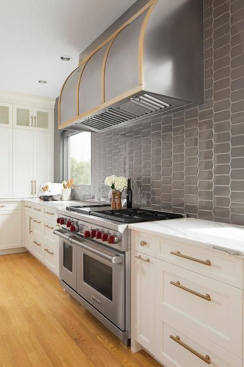 A Silver And Gold Barrel Range Hood Is Fixed To Dark Gray Oval Backsplash Tiles Above A Wolf Dual Range Flan Kitchen Remodel Diy Kitchen Remodel Kitchen Design