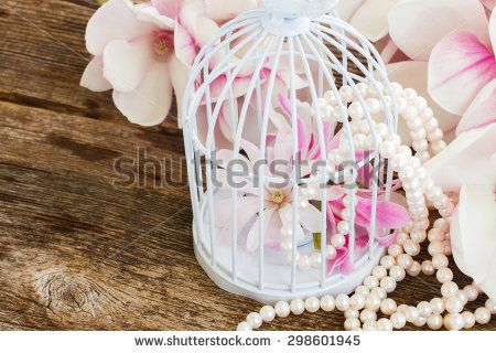 pink magnolia flowers with pearls  and birdcage on wooden table