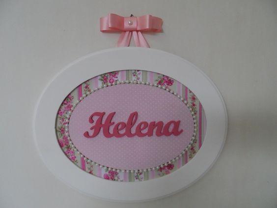 Quadro oval G, feito de MDF, fundo forrado com tecido de algodão, nome em MDF pintado de rosa, decorado com colar de pérolas. Para pendurar laço channel. R$ 93,00