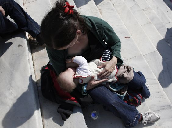 A mother breast-feeds her baby during an event in central Athens in November.