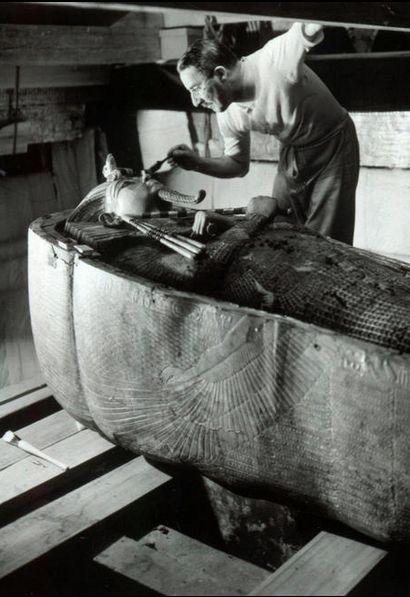 Discovery of the Tomb of Tutankhamun, Howard Carter working on the lid of the second (middle) coffin still nestled within the case of the first (outermost) coffin in the Burial chamber, October 1925, photographed by Harry Burton, Egypt.
