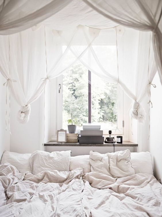 A cozy, canopy room that is settled with neutral colors. This room just looks so relaxing and calming. I love the window that is up against the bed.