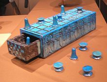 Ancient Egyptian Game of Senet.  The color reminds me of Egyptian paste clay that glazes itself when it's fired.  I'm wondering if the tokens, at least, are made from it.