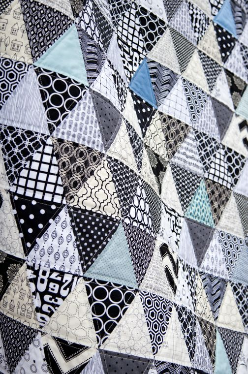"""15 different white prints, 15 different black prints and 8 different blue solids and prints to make up this quilt. Each triangle measures 4"""" and the overall size of the quilt is 60"""" x 72""""."""