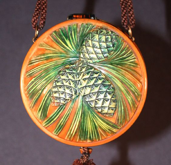 A wonderful grouping of pineconesgrace thiscelluloid dance purse. Pinecones are a common theme in Arts and Crafts pieces, but there are only a few celluloid purses that feature them.