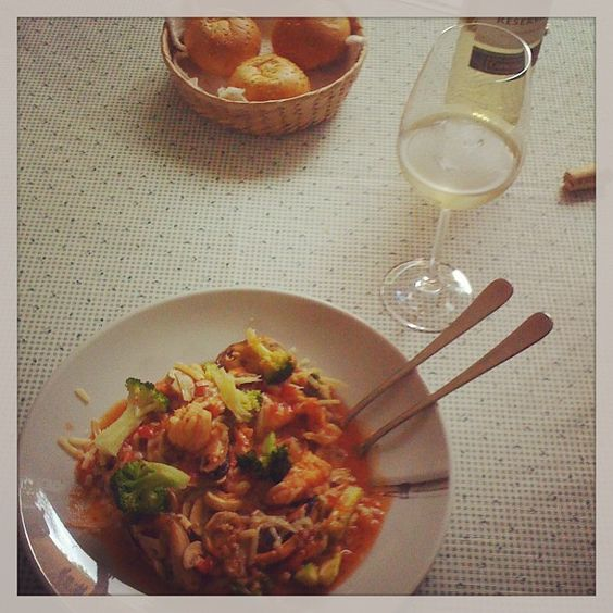 not completed alone : Pasta with shrimps and veggies. Glass of white wine