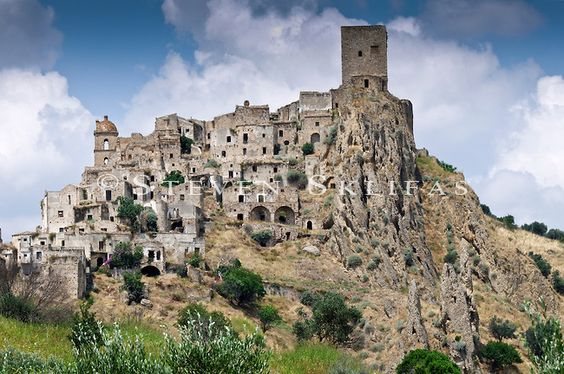 Italy. Basilicate. Craco. Picturesque view of the medieval hilltop ghost town of Craco which is dominated by its magnificent Norman period tower. Scenically rising above its mesmerizing landscape, the town overlooks the Cavone river valley in the region of Basilicate in southern Italy. Founded around 500 AD, the town which is in a seismic active area was completely abandoned by its population in 1991 when a succession of landslides threatened to ruin the town and its people.
